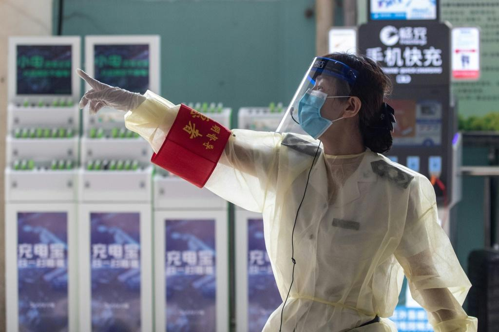 A staff member wearing a face shield points instructions at a bus station in Wuhan in China's central Hubei province