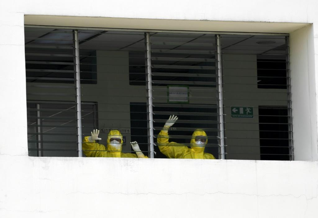 Health workers celebrate as they watch a 16-year-old patient who recovered from COVID-19 leave hospital in Santa Tecla, El Salvador