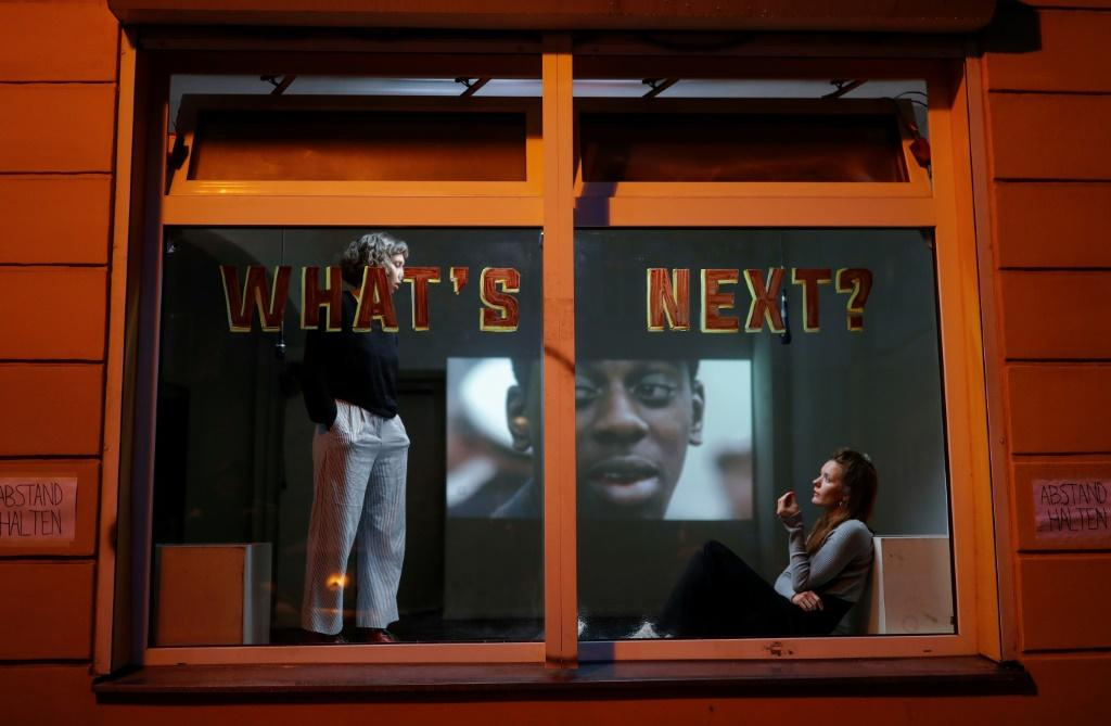 Performance artists put on a show in a window of a house in the Liebig Steet in Berlin's Friedrichshain district