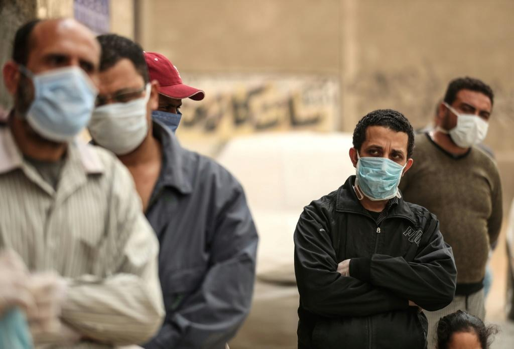 Men wait outside a centre of the non-governmental Egyptian Food Bank to receive cartons with foodstuffs in April