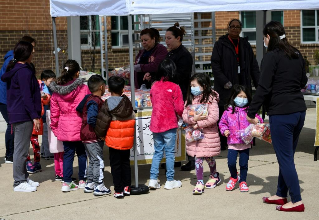 Children pick up free lunch in Arlington, Virginia on March 16, 2020, after schools closed due to coronavirus. Disrupted school lunch programs could be a factor in alarming rises in hunger among US children since the outbreak began, the study says