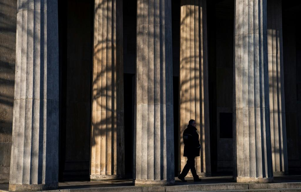 A guard walks past the columns of a memorial in Berlin that will figure in VE day ceremonies