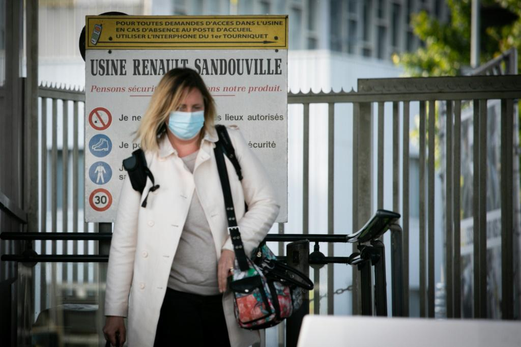 A woman wearing a face mask leaves the plant of the French Renault car maker in Sandouville, northern France, on May 7, 2020; the Le Havre judiciary courthouse has said French car maker Renault must suspend a return to production during the COVID-19 pande