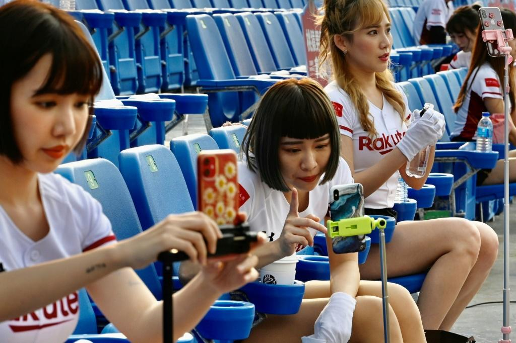 Cheerleaders are using their phones to interact with fans