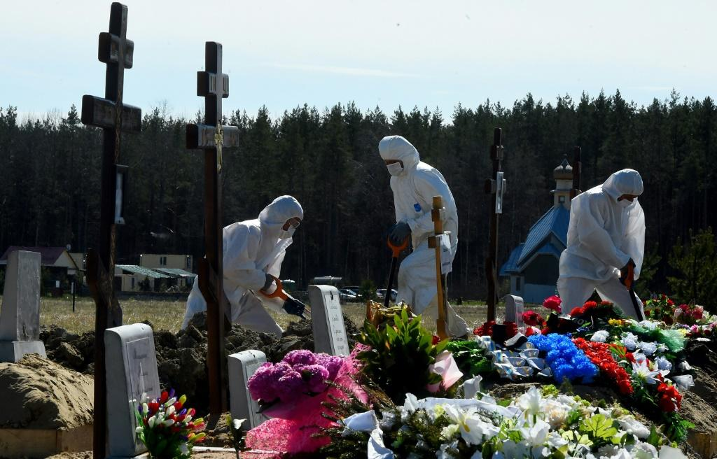 Cemetery workers wearing protective gear bury a coronavirus victim at a cemetery on the outskirts of Saint Petersburg on May 6, 2020