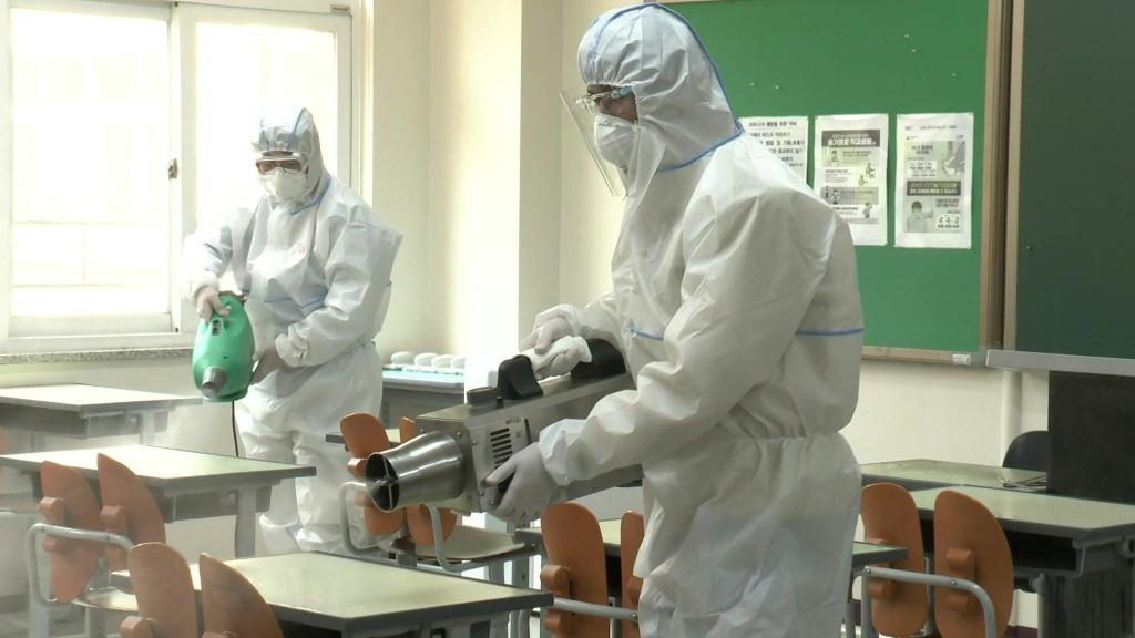 Health officials disinfect a high school in Seoul as schools are set to re-open, firstly to high school seniors, following the government's decision to relax coronavirus restrictions.