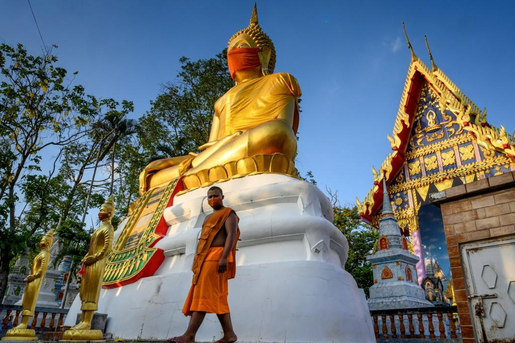 A monk walks in front of a giant Buddha statue wearing a face mask at Wat Nithet Rat Pradit temple in Pathum Thani outside Bangkok