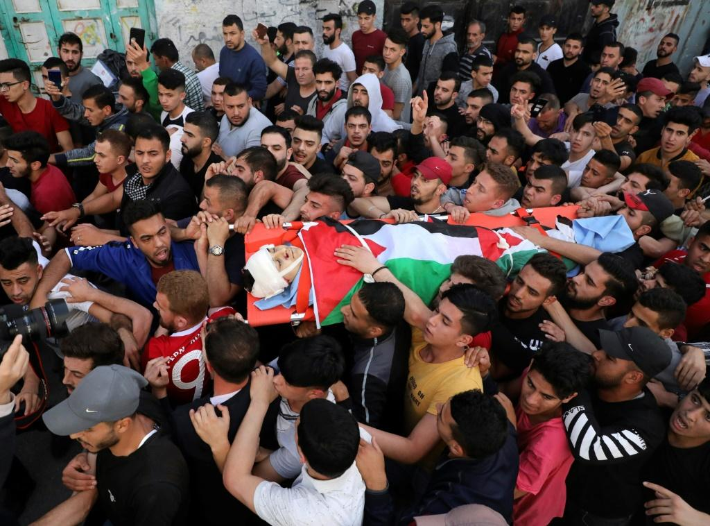Palestinian mourners carry the body Zaid Qaysia, 15. Israeli forces shot dead the teenager during clashes in the occupied West Bank, the Palestinian health ministry said