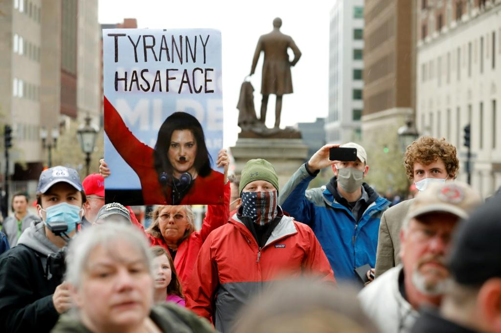 A Hitler moustache drawn on a picture of Michigan Governor Gretchen Whitmer on a sign held by a protestor at an anti-lockdown demonstration in Lansing, Michigan