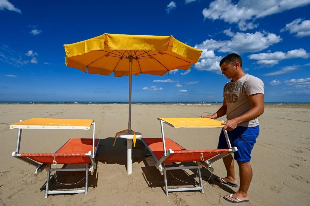A beach manager spaces out sunbeds on the seafront of Cesenatico on the Adriatic coast