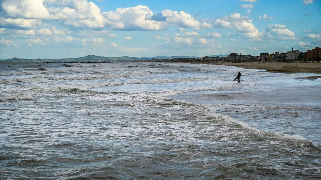 Only a few surfers take the opportunity to hit the waves in Rimini