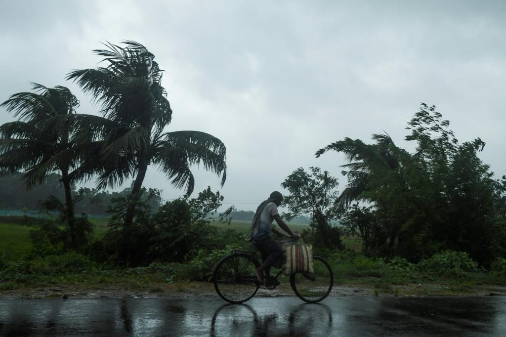 A man rides a bicycle under the rain ahead of the expected landfall of Cyclone Amphan in Midnapore, West Bengal, on May 20, 2020