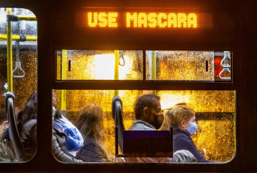 """Commuters wearing face masks travel on a public bus with an electronic sign reading """"Wear a face mask"""", in Curitiba, Brazil on May 22, 2020"""