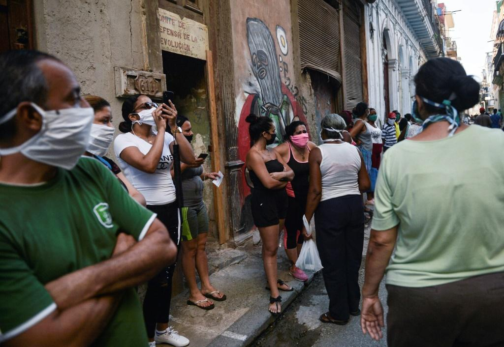 People wear face masks as they queue to buy food in Havana on May 19, 2020, amid the new coronavirus pandemic. US President Donald Trump has ramped up tensions with the island nation after a relaxation during the Obama years