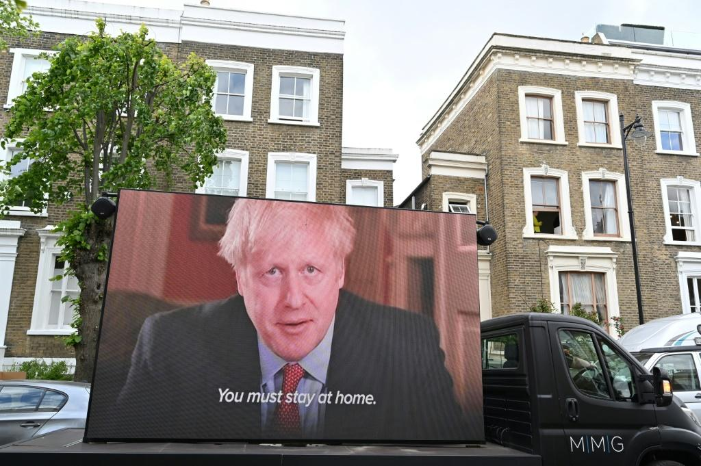 A big screen organised by British political campaign group Led By Donkeys, plays a clip from Prime Minister Boris Johnson's March 23 address to the nation outside the home of Dominic Cummings