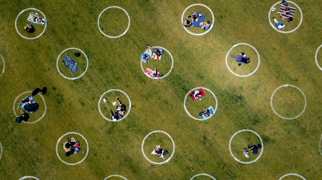 An aerial view shows painted circles in the grass to encourage people to social distance at Washington Square Park in San Francisco, California