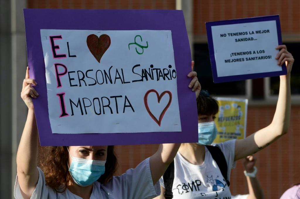 """A healthcare worker in Spain holds a sign reading """"Healthcare workers matter"""