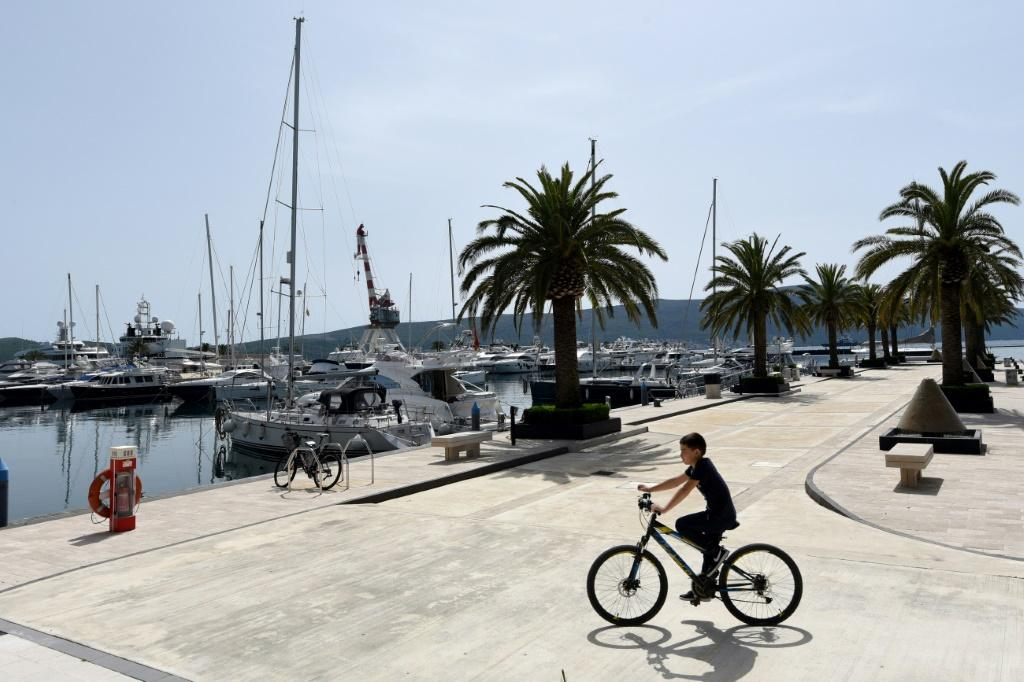 A solitary cyclist rides at the eerily quiet Porto Montenegro marina