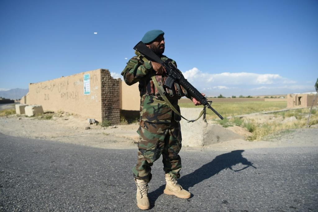 An Afghan National Army (ANA) soldier stands guard at a checkpoint in Bagram district as Taliban prisoners are released from the Bagram prison