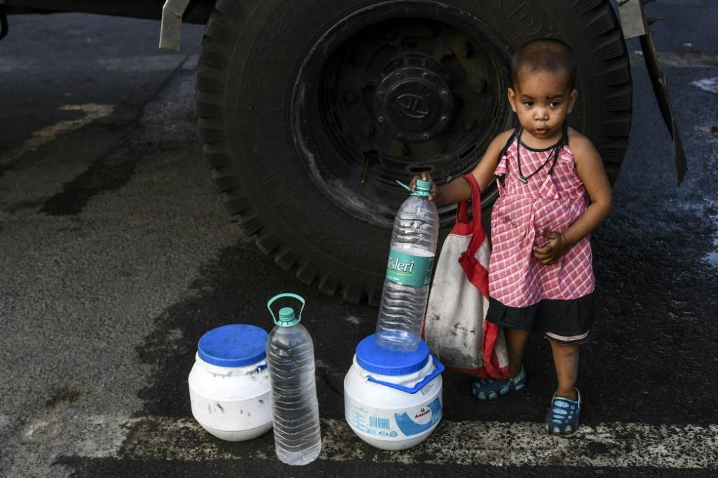 A child stands next to bottles and cans as her mother collects water from a tanker in New Delhi as the Indian government eases a nationwide lockdown