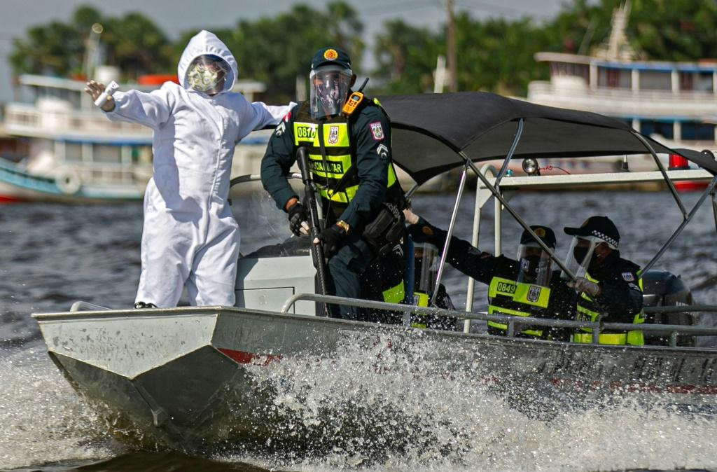 A government medical worker, in a joint operation with military police, prepares to check passengers on boats in the Melgaco bay, Brazil