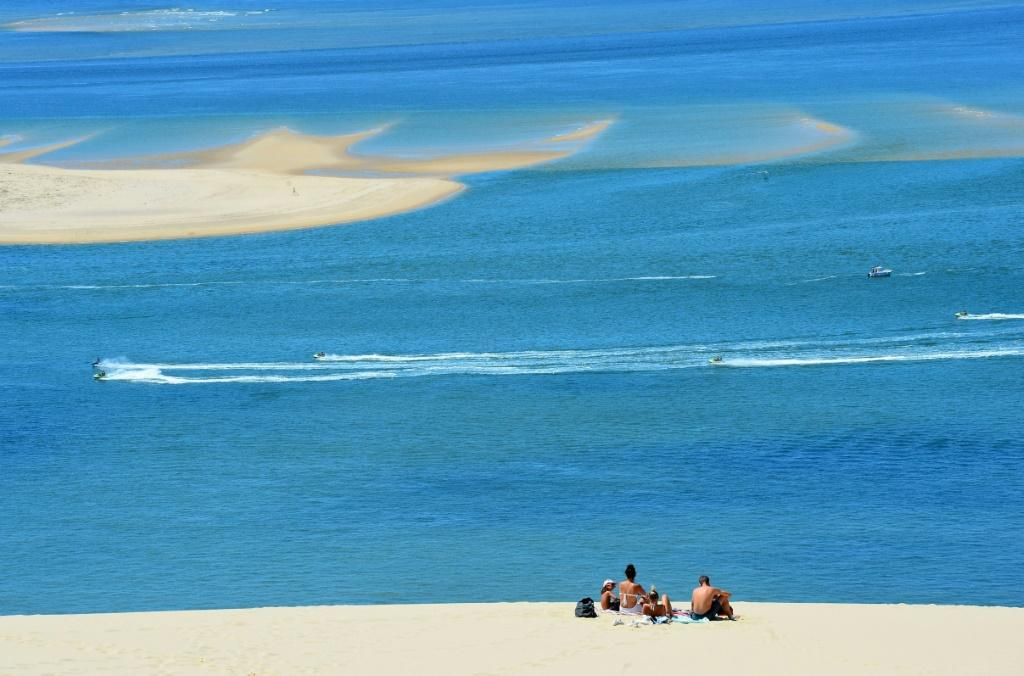 People enjoy a sunny day atop Europe's tallest sand dune, the