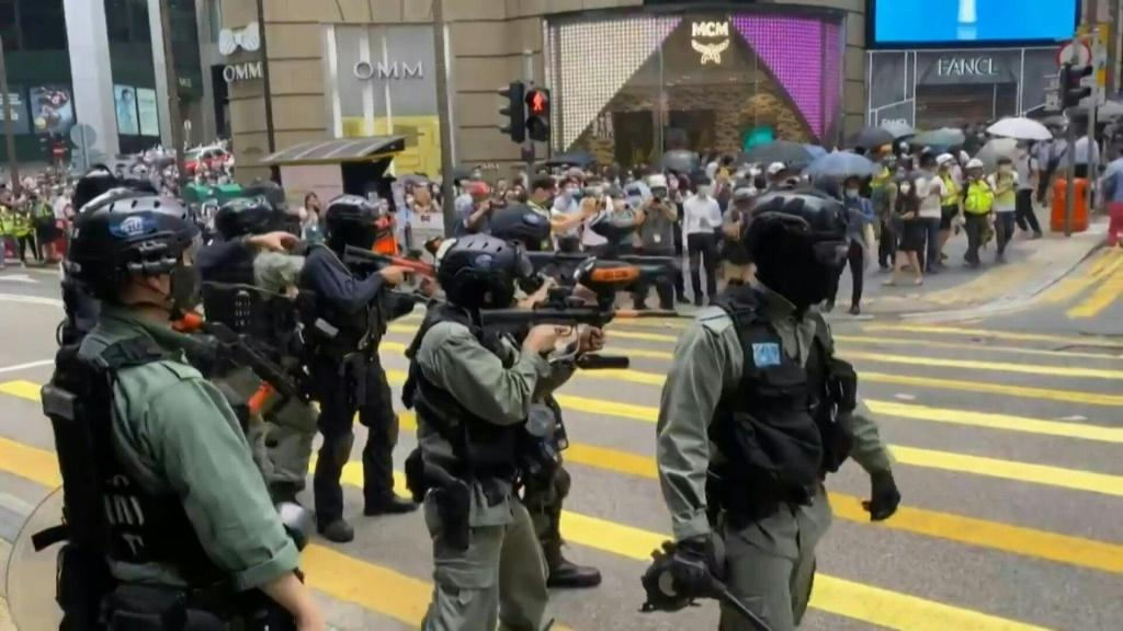 Riot police in Hong Kong fire pepper-ball rounds in the central commercial district as they try to stamp out protests against a bill banning insults to China's national anthem.