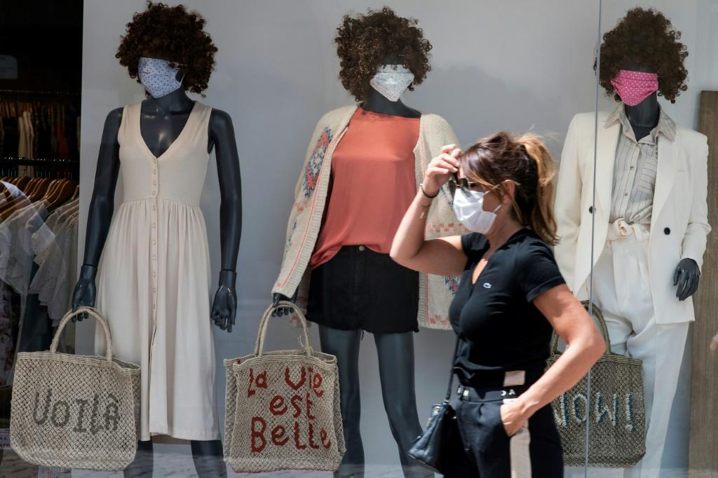 A woman wearing a face mask passes by a show window with masked mannequins in Mulhouse, eastern France