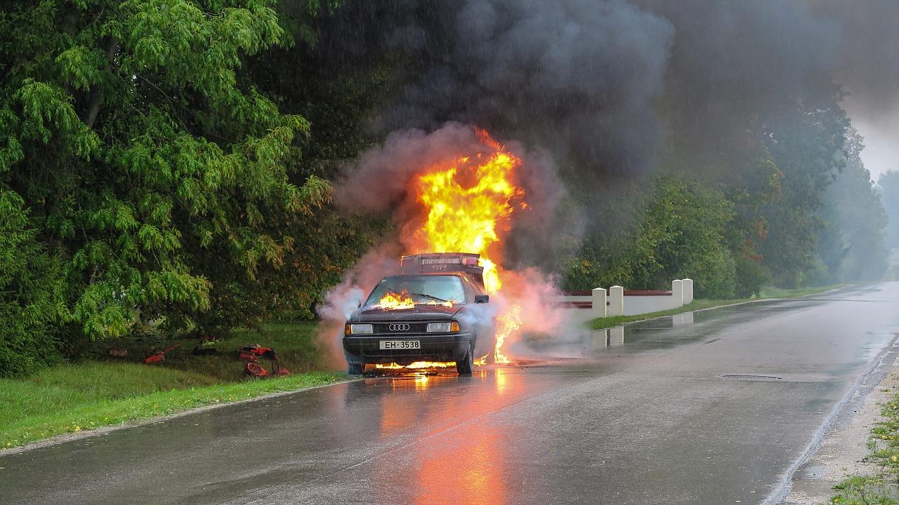 man drags driver away from burning car