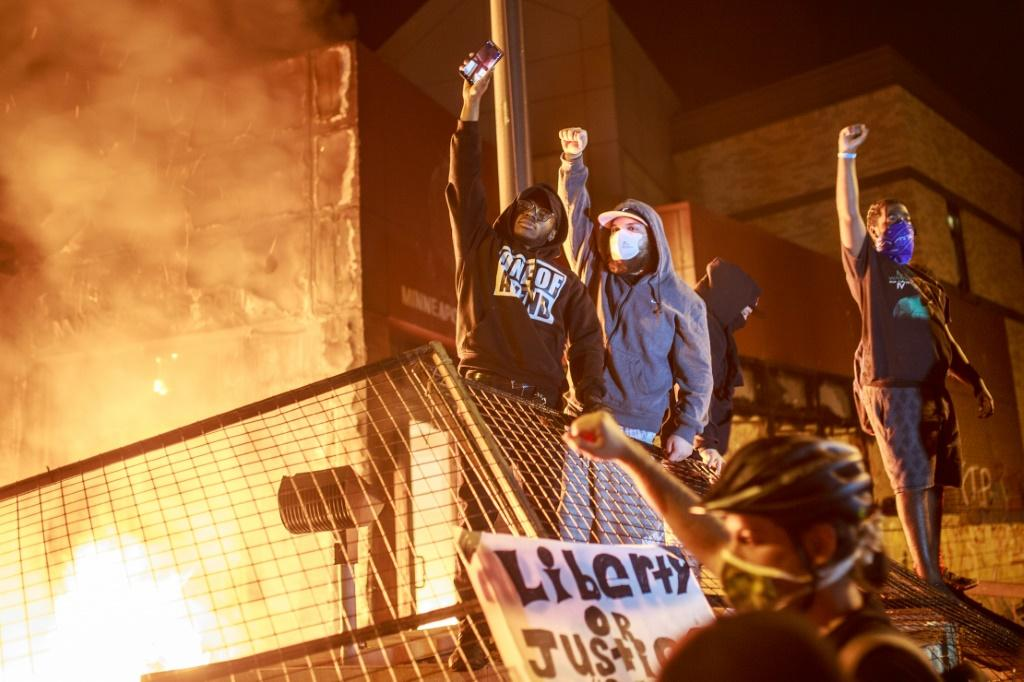Protesters hold up their fists as flames rise behind them in Minneapolis, Minnesota, during a protest over the death of African American George Floyd in police custody