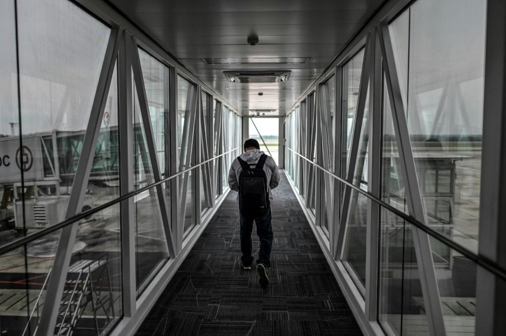 A passenger walks along an airbridge at Tianhe Airport in Wuhan