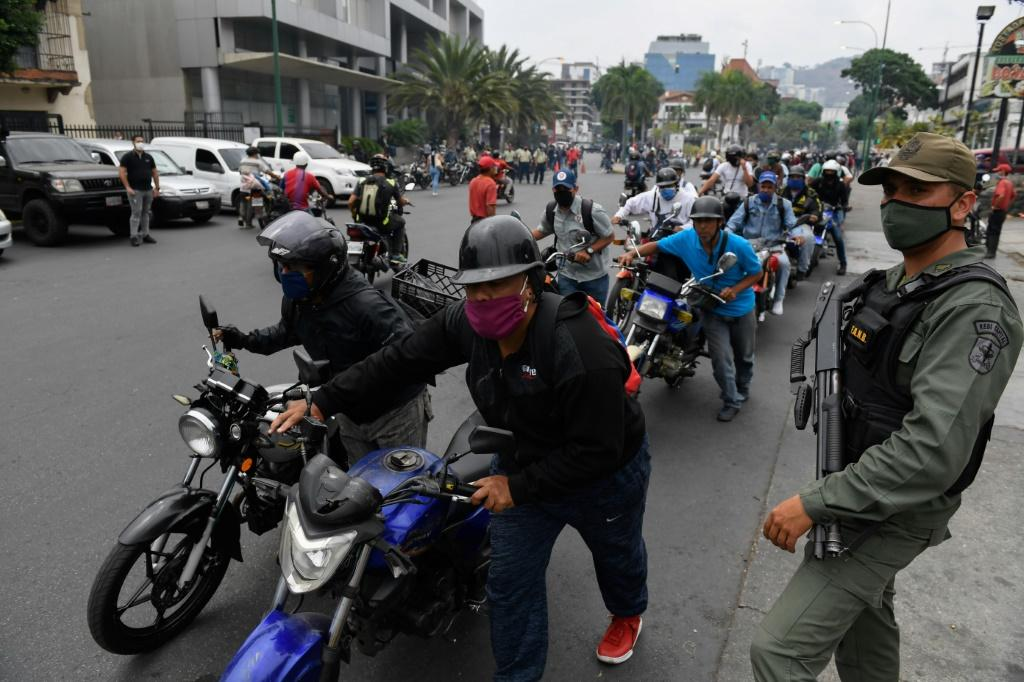 A soldier stands watch in Caracas, Venezuelas as bikers queue up to refuel amid a nationwide shortage