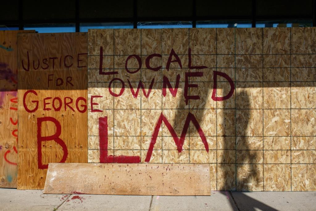 "Business owners have boarded up their shops with panels that read ""Justice for George,"" ""Kids live here"" or ""Minority Owned,"" in an attempt to deter protesters"