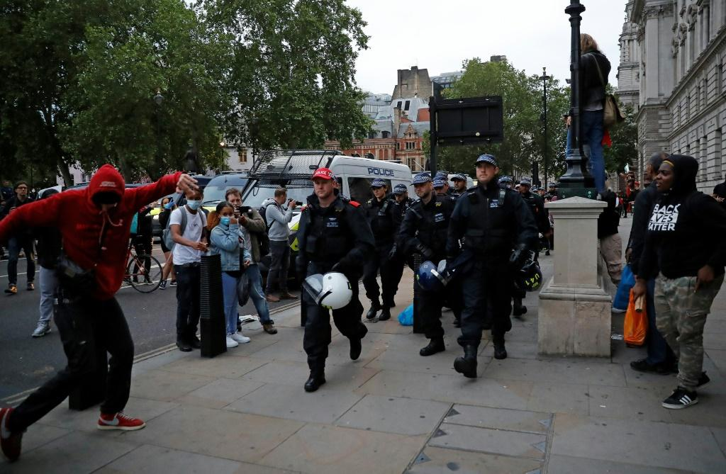 Protestors watch as police officers carrying riot helmets walk along the street near Parliament Square during an anti-racism demonstration in London after George Floyd, an unarmed black man, died in police custody Minneapolis, USA.