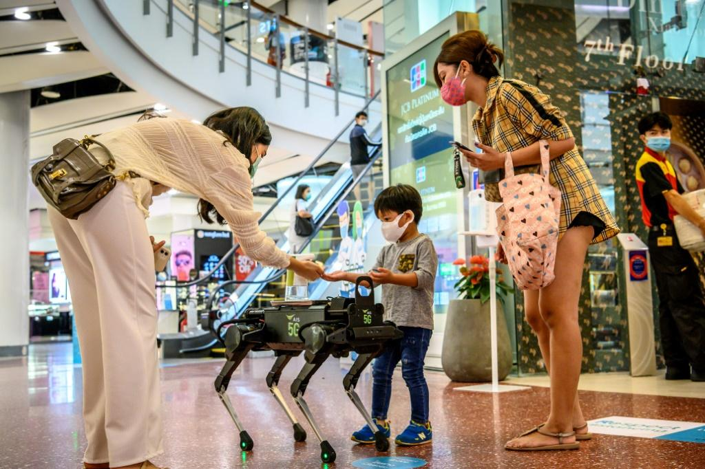 A 5G K9 robot distributes hand sanitiser to visitors in a shopping mall in Bangkok