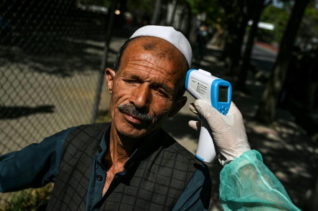A man has his temperature checked by a health worker at the Wazir Akbar Khan mosque in Kabul