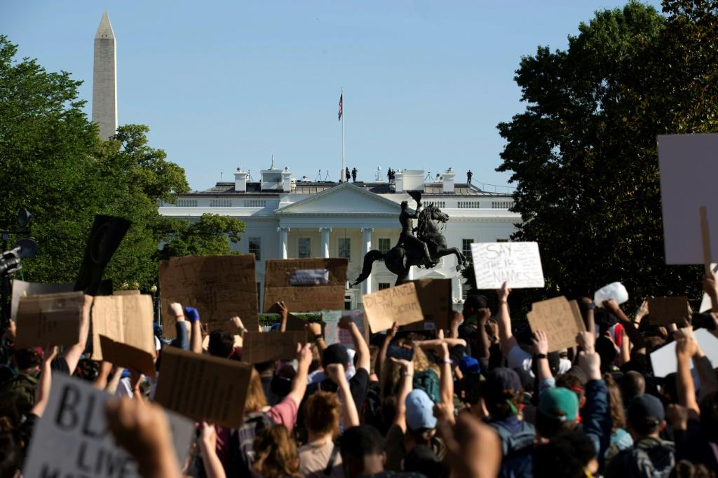 Demonstrators holding signs protest outside the White House over the death of George Floyd