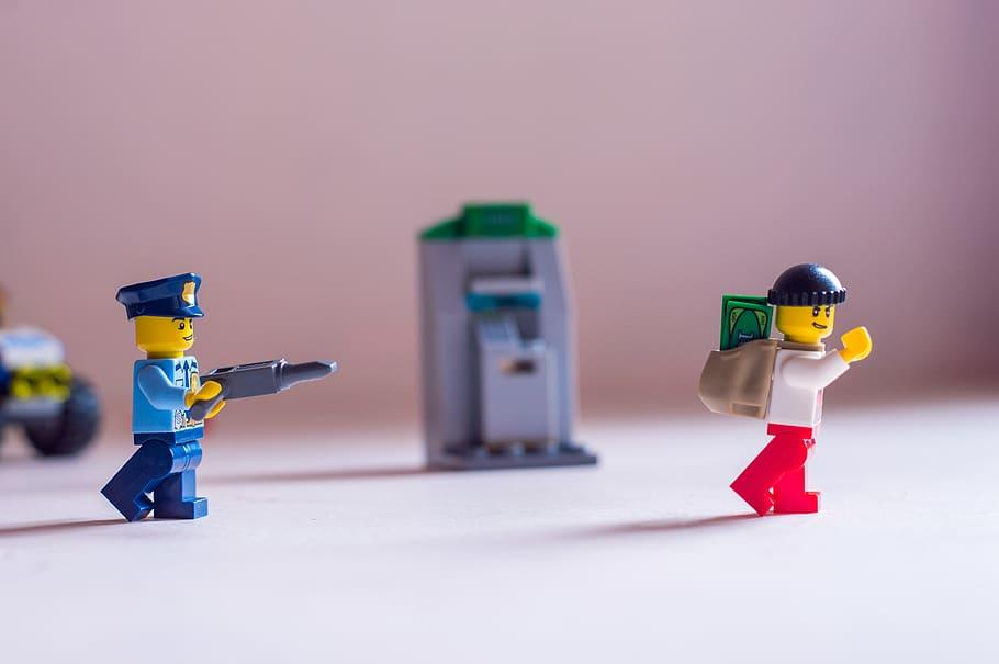 a-lego-police-officer-pointing-his-gun-at-a-robber