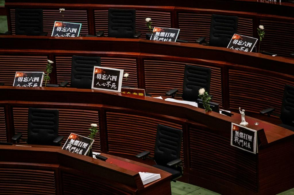 Placards and flowers are left in front on empty seats as pro-democracy legislators walk out of the chamber as debate continues in Hong Kong on June 4, 2020, ahead of a vote over a law that bans insulting China's national anthem