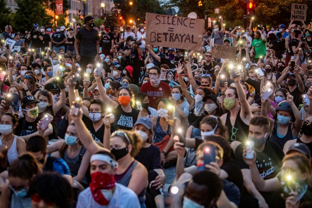 Protesters hold up their phones during a demonstration over the death of George Floyd, outside the White House in Washington, DC