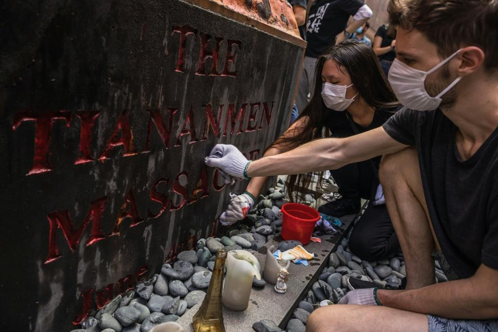 students clean the Pillar of Shame, a statue by Danish artist Jens Galschiot to remember the victims of the 1989 Tiananmen crackdown