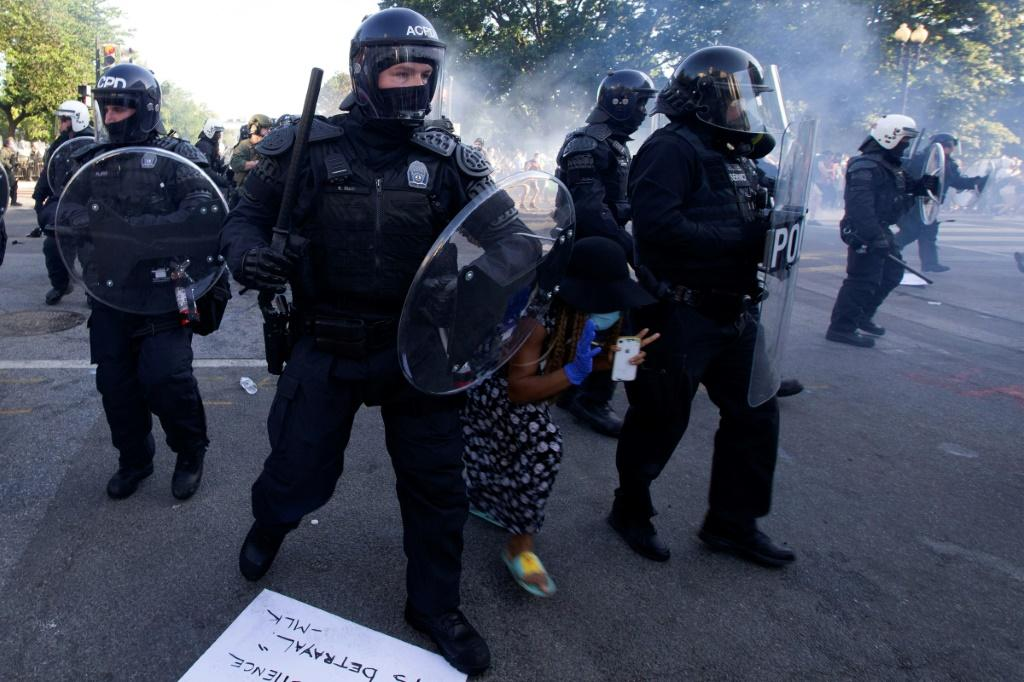 A demonstrator tries to pass riot police as they push back demonstrators outside the White House, June 1, 2020 in Washington DC