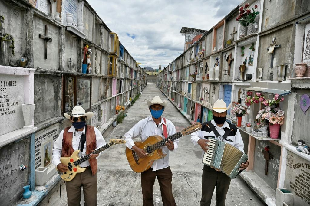Humberto Montes (C) with musicians Roberto Maldonado (L) and Israel Mundo (R), wait to offer their services before a funeral at the municipal cemetery in Ciudad Nezahualcoyotl on June 3