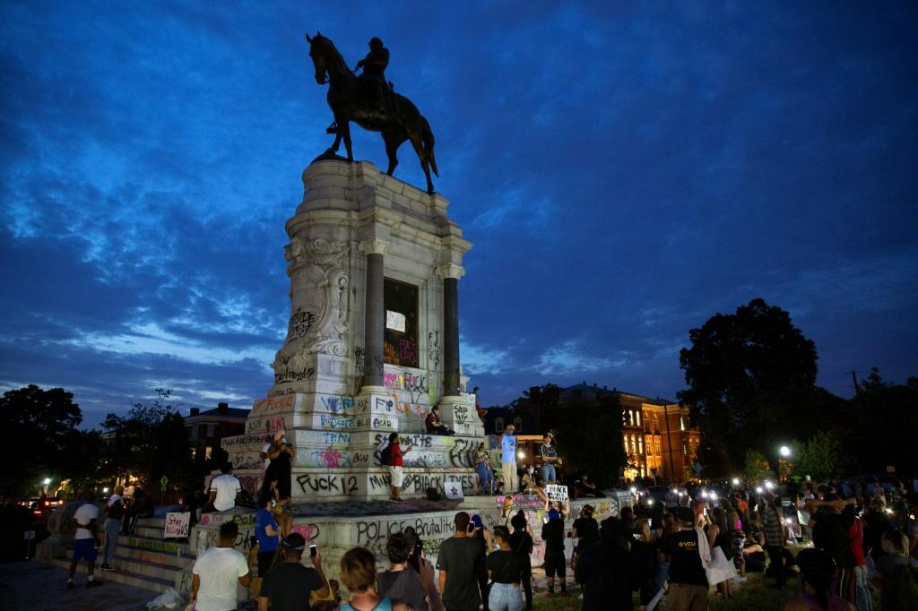 Protestors surround the statue of Confederate general Robert E. Lee in Richmod which the Virginia governor announced would be removed 'as soon as possible'