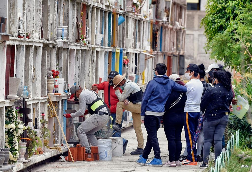 Worker Daniel Angeles (L) during an inhumation at the municipal cemetery in Ciudad Nezahualcoyotl