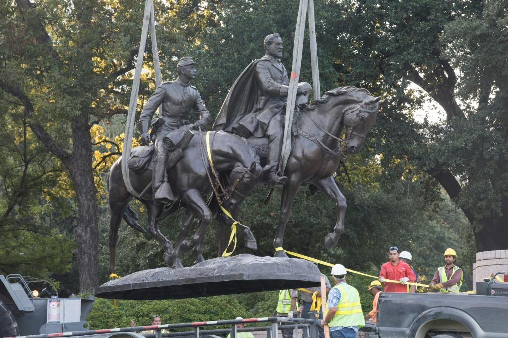 Workers remove statues of Confederate generals from a park in Dallas, Texas, in September 2017