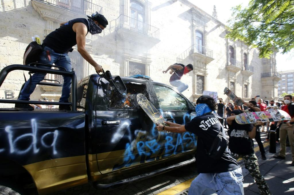 Demonstrators attack a police vehicle during a protest in Guadalajara, Mexico