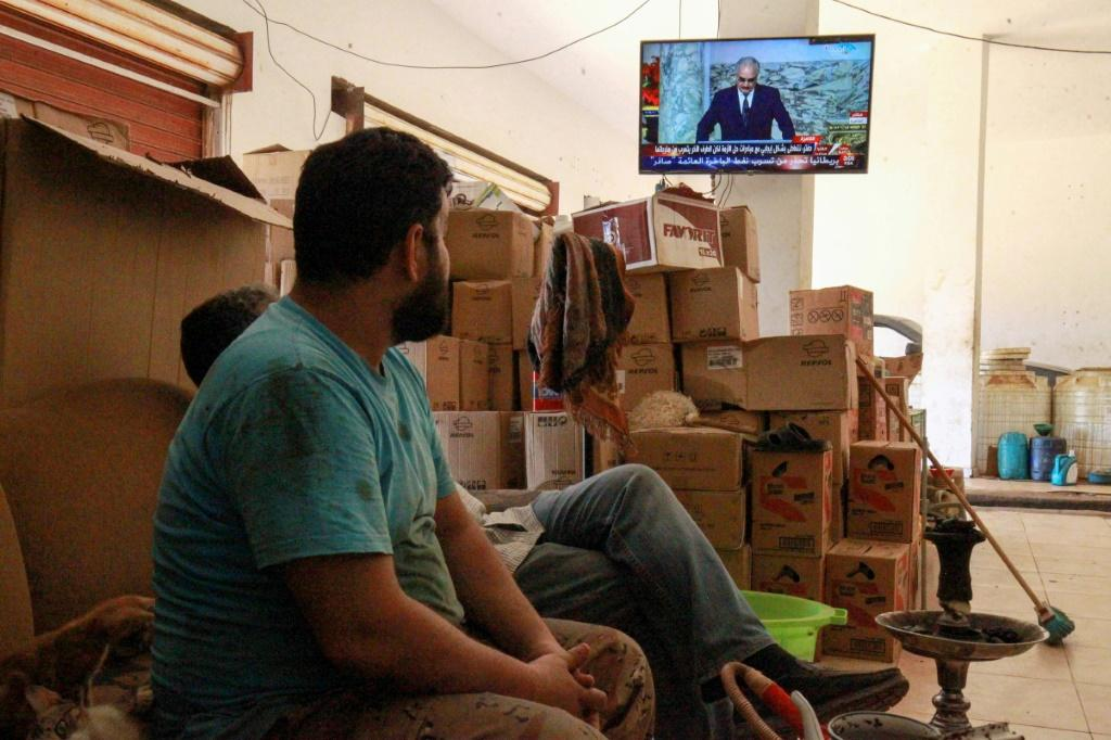 Libyans in the eastern port city of Benghazi watch a televised speech by strongman Khalifa Haftar, whose forces have lost significant ground to a UN recognised government in recent weeks