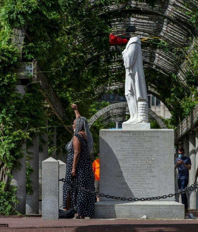 A woman poses in front of a decapitated statue of Columbus at Christopher Columbus Park in Boston, Massachusetts on June 10