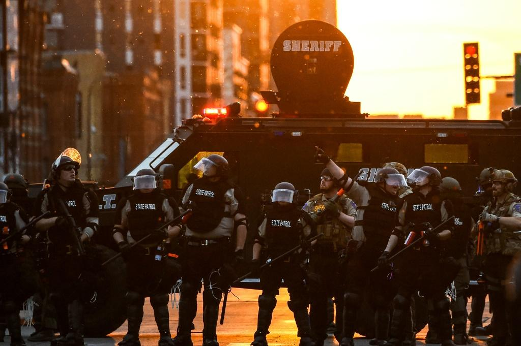 Minnesota State Police officers in front of an armored sheriff's vehicle on May 31, 2020 in Minneapolis, during a protest against police brutality after the killing of George Floyd days earlier